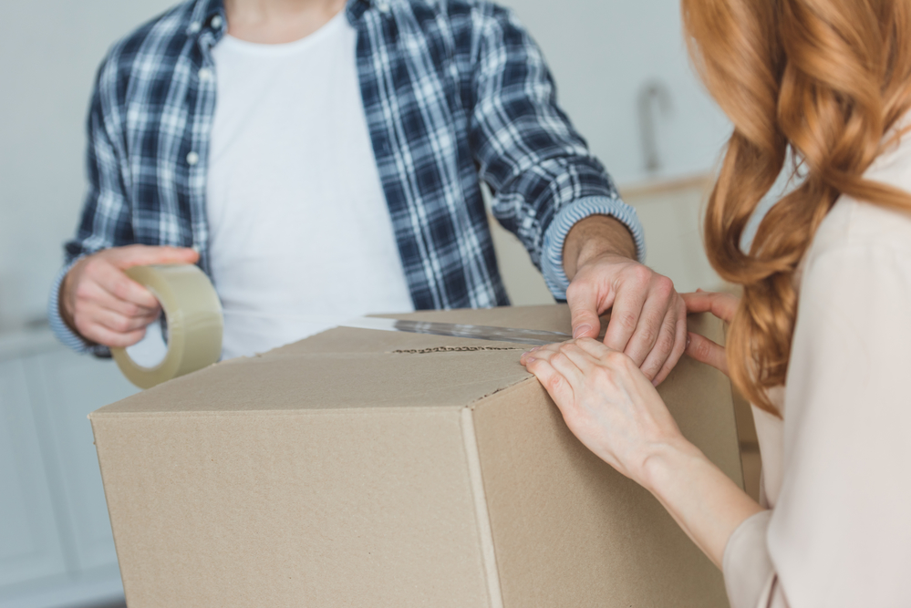 Couple packing a box to move house